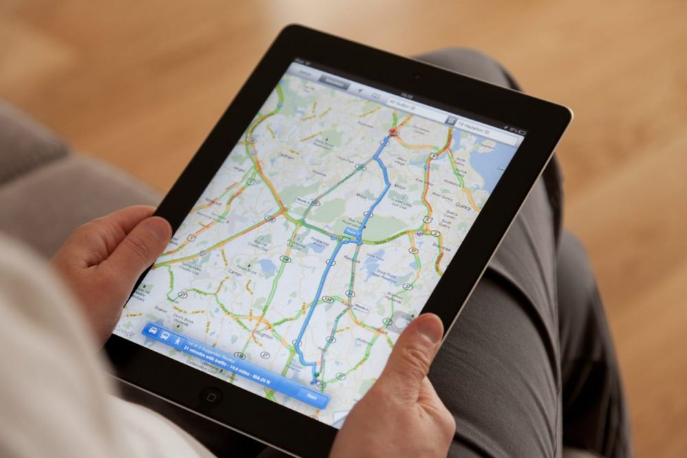 person holding tablet and using map feature