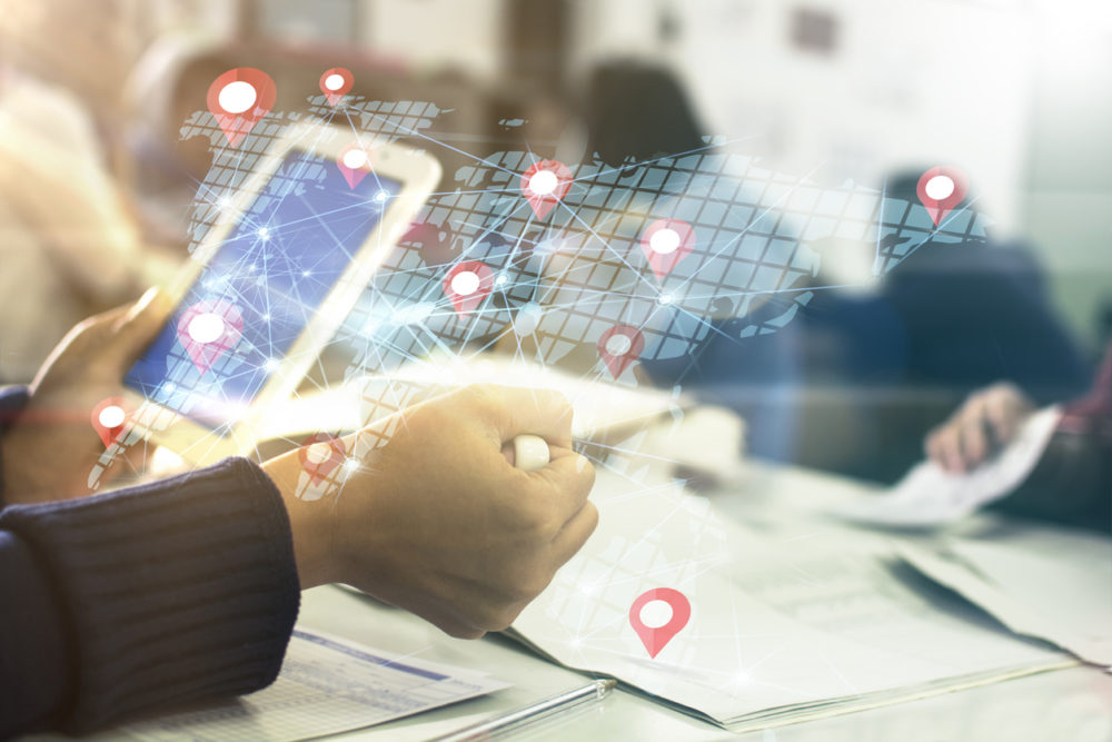 Man in a business setting using a tablet device showing multiple navigation locator icons while targeting potential customers.