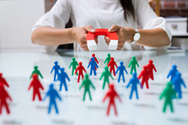 Lead generation concept, woman holding a magnet to attract customers for the company.